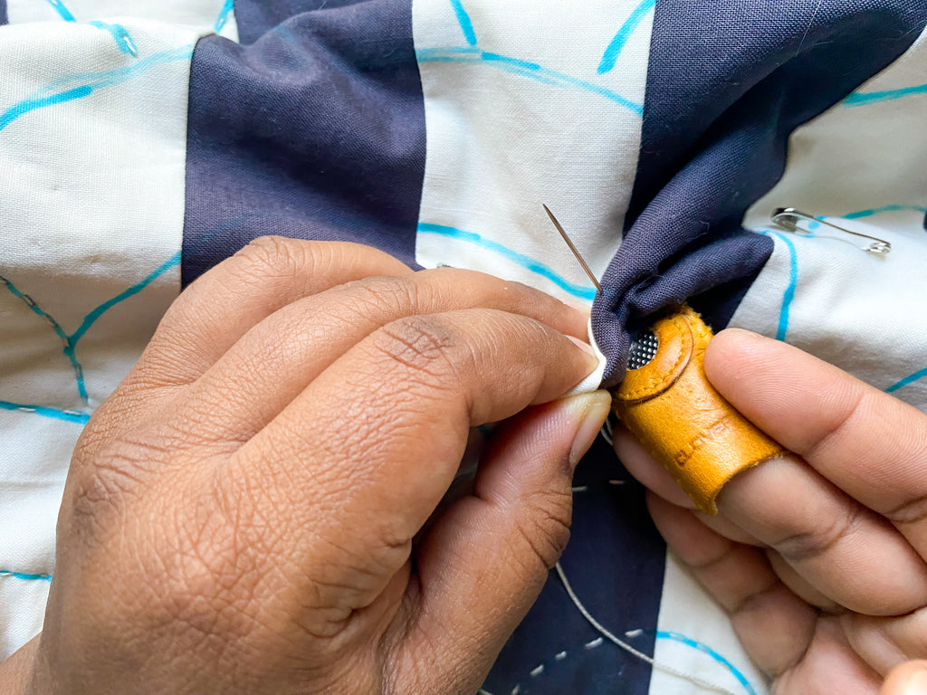 using a thimble and middle finger to push needle through quilt