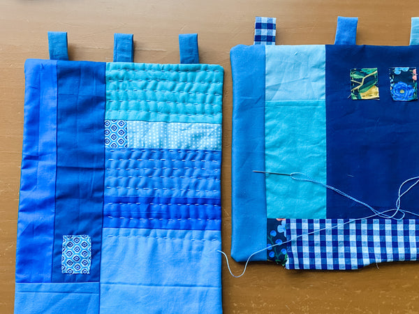 two improv quilted wall hangings in blue