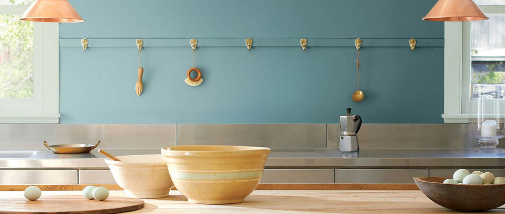 modern kitchen with blue wall and island with bowls