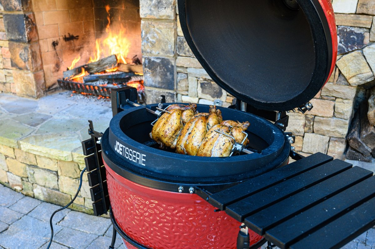 A JoeTisserie being used on a Kamado Joe grill next to a backyard fireplace