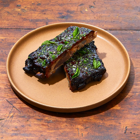 Beautifully charred Baby Back ribs garnished with fresh herbs