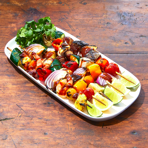A plate of grilled skewers with red onions, tomatoes, peppers, steak, fish, and veggies, plus 'nade for dipping