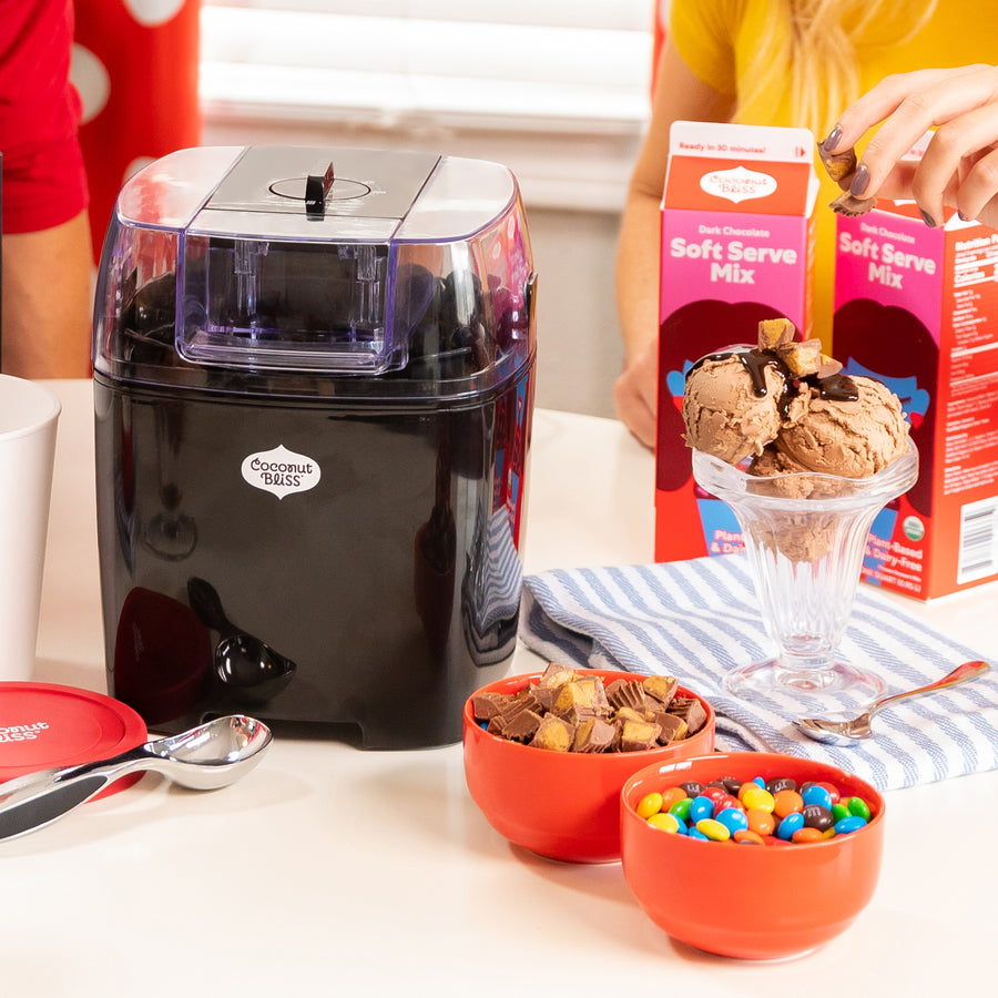 Black ice cream maker on a tabletop with toppings and a sundae.