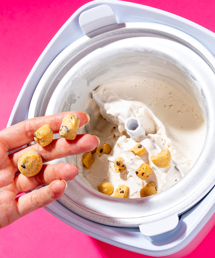 Hand placing cookie dough into an ice cream mixer full of vanilla ice cream.