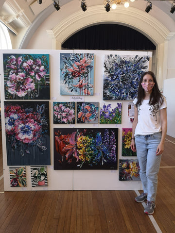 Judy Century Art Standing beside gallery wall display at Big Art Fair Exhibition at Hitchin Town Hall