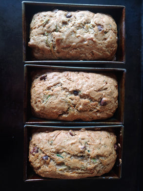 Three loaves of chocolate chip zucchini bread in baking trays.
