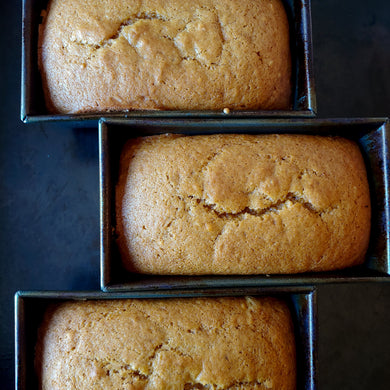 Three loaves of pumpkin bread in baking tins.