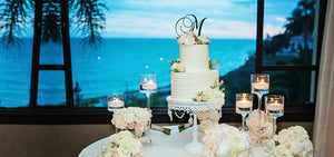 tiered white wedding cake with monogram cake topper on white chandelier cake stand for ocean view wedding