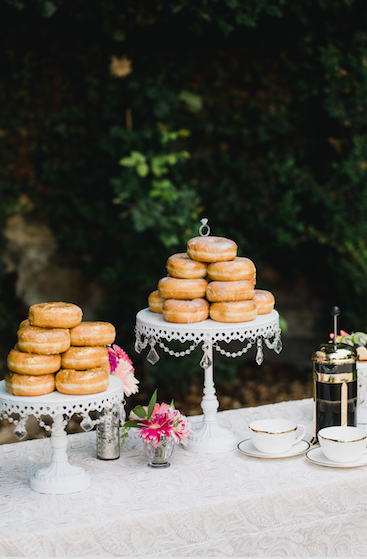 white chandelier cake stands with wedding donuts on dessert table