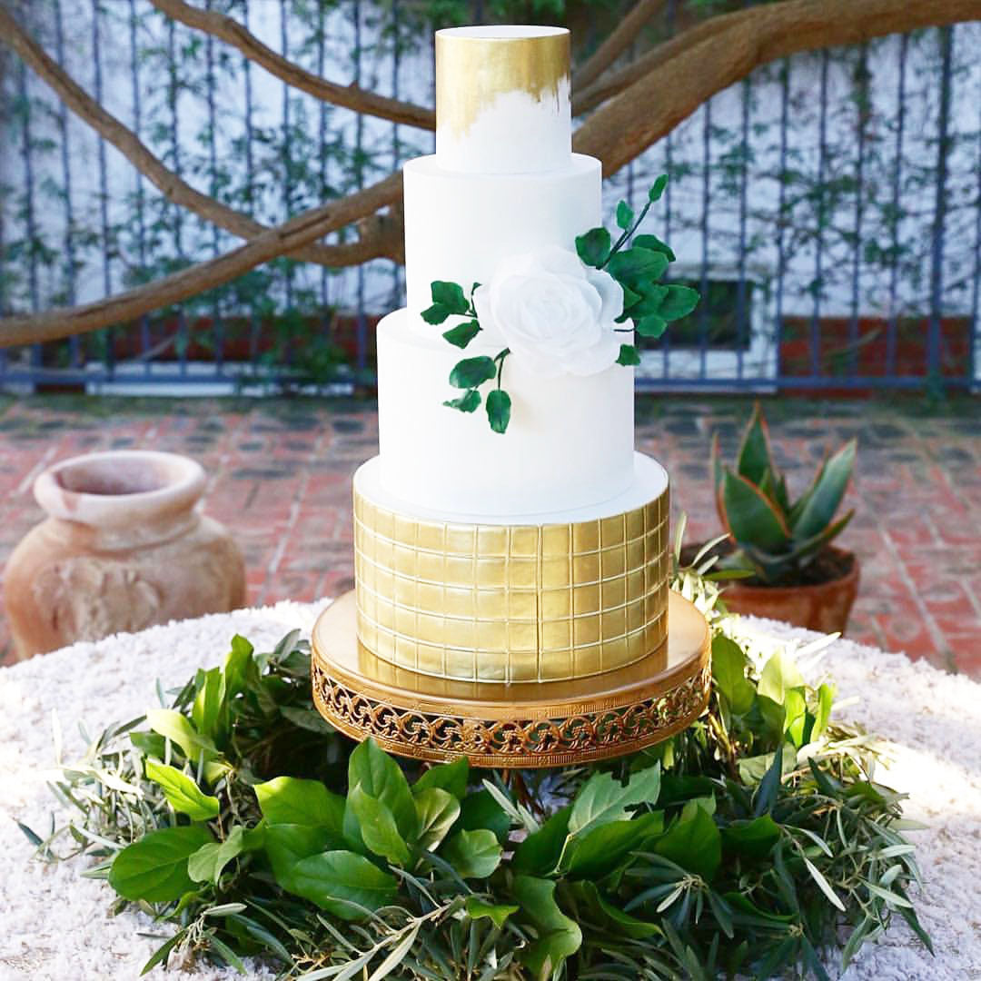gold foil wedding cake on gold cake stand with greenery