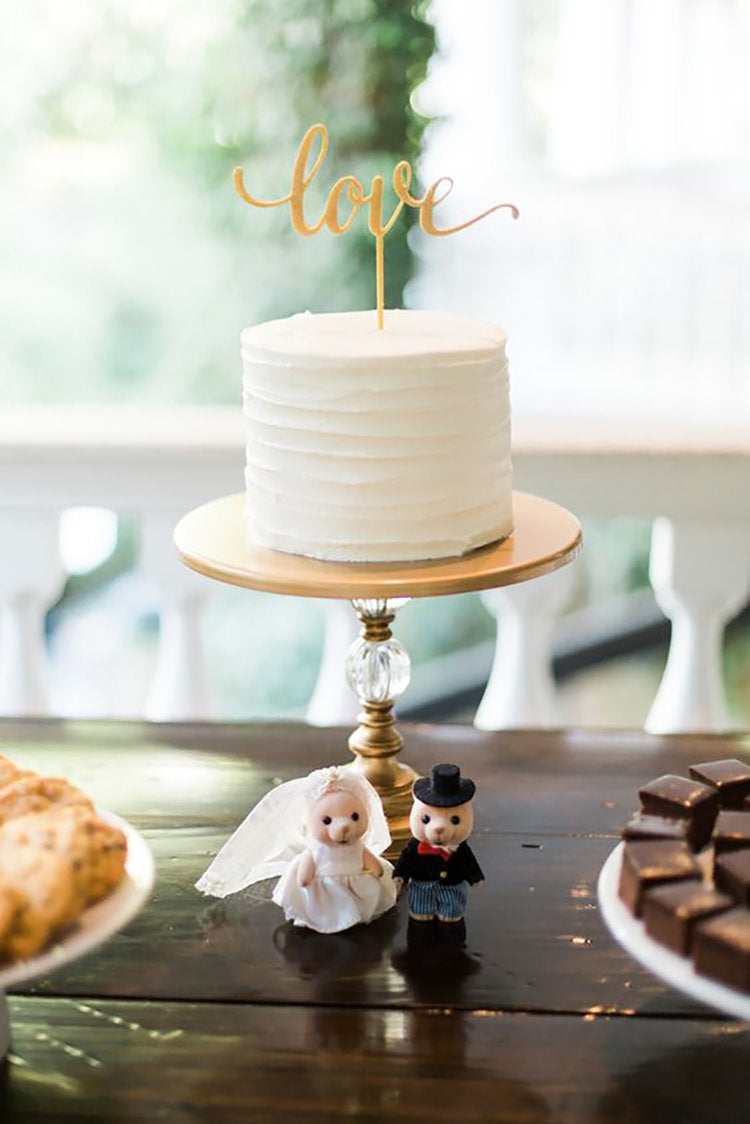 small simple white wedding cake with love cake topper