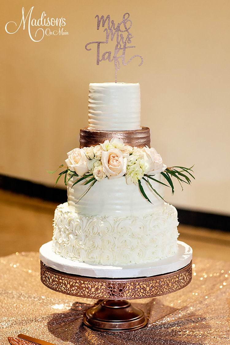 traditional white tiered wedding cake on rose gold cake stand
