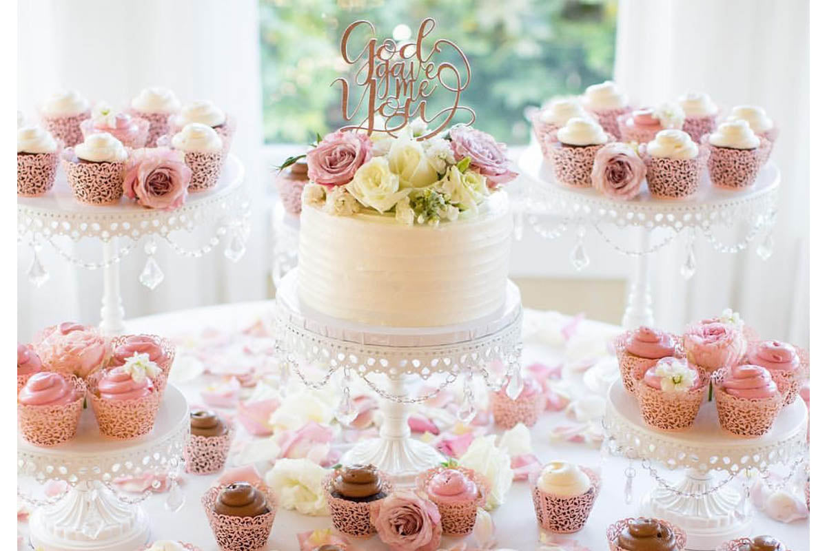 wedding cake and cupcakes on table