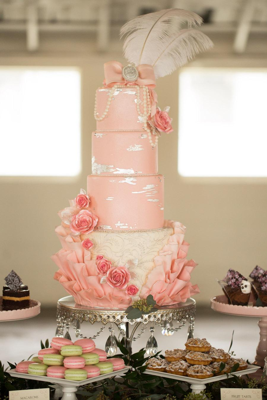 pink wedding cake on silver chandelier cake stand