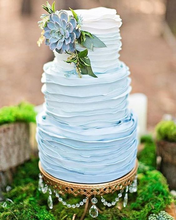 blue ombre wedding cake on gold chandelier cake stand