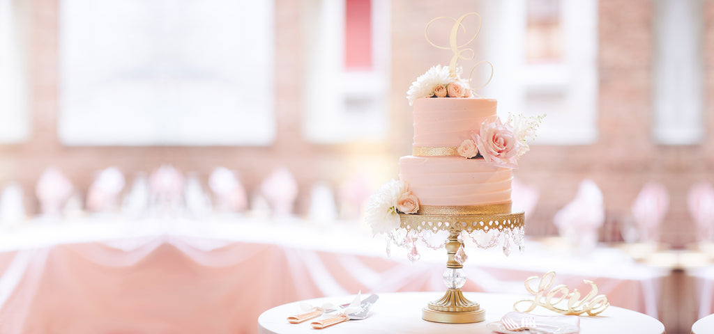 pretty pink tiered cake on gold chandelier cake stand