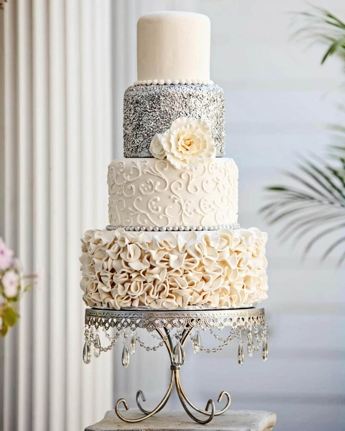 wedding cake with 4 tiers on silver chandelier cakestand