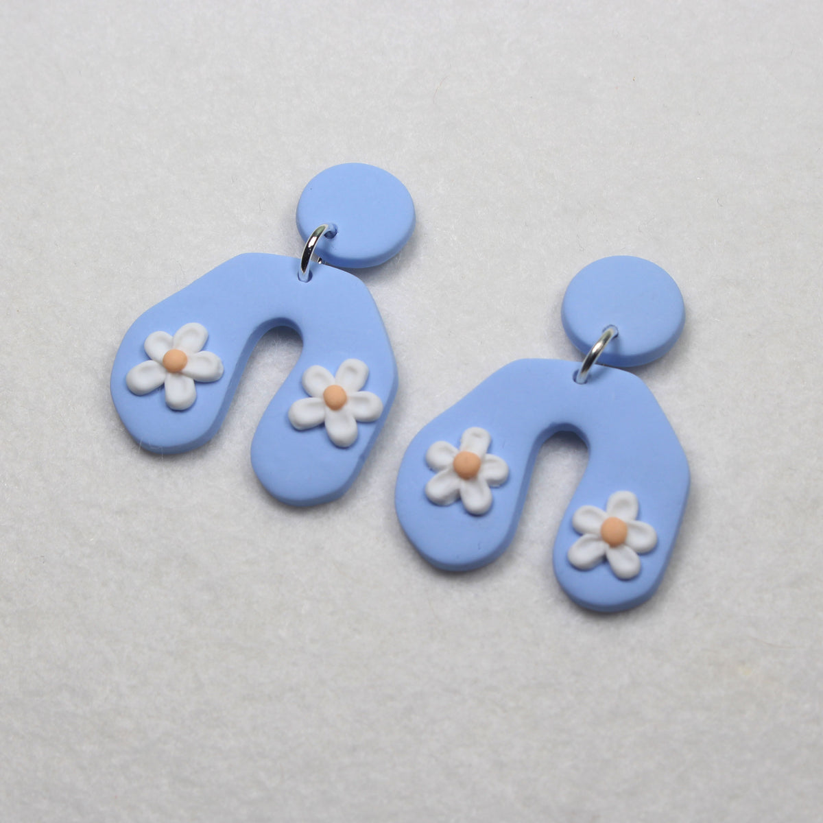 nickel free stud earrings made from polymer clay. white daisies on a pastel blue background