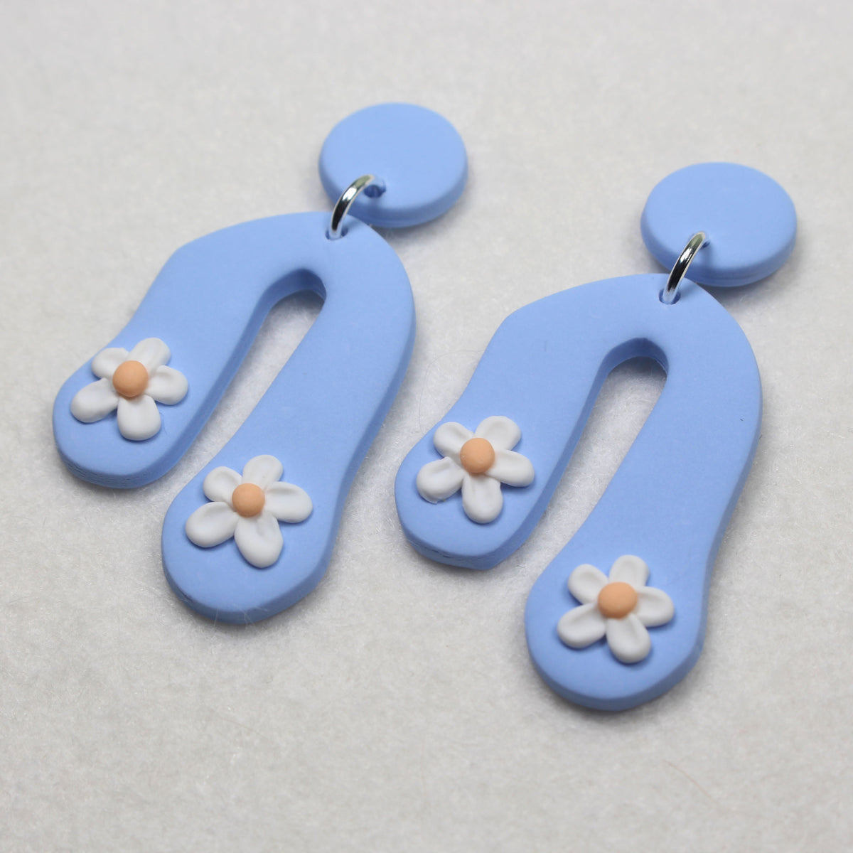 polymer clay stud earrings. hand sculpted daisies on a baby blue background.