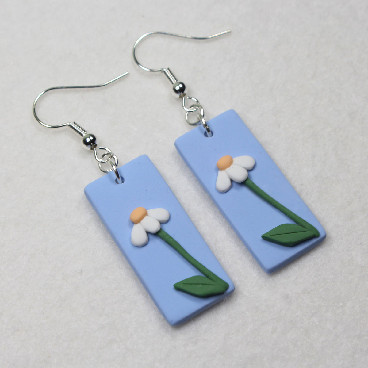 simple daisy earrings, with stem and leaves, standing tall on a pastel blue background as part of the daisy fields polymer clay earrings collection