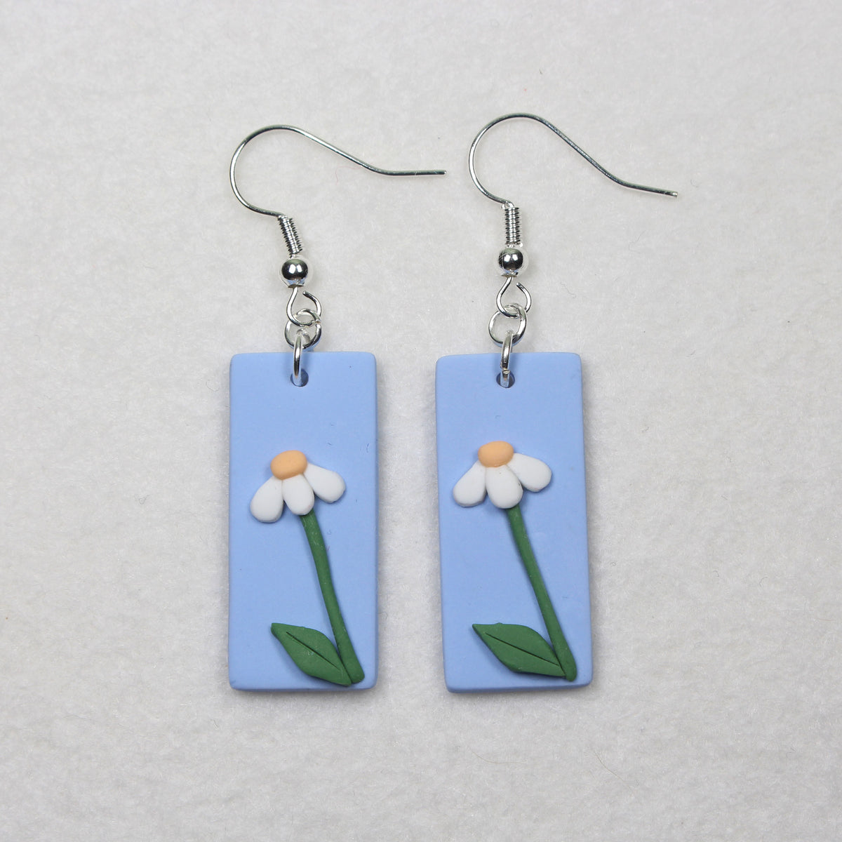 Daisy in the Wind Hook Earrings. Tall daisies with stem and leaves standing in field