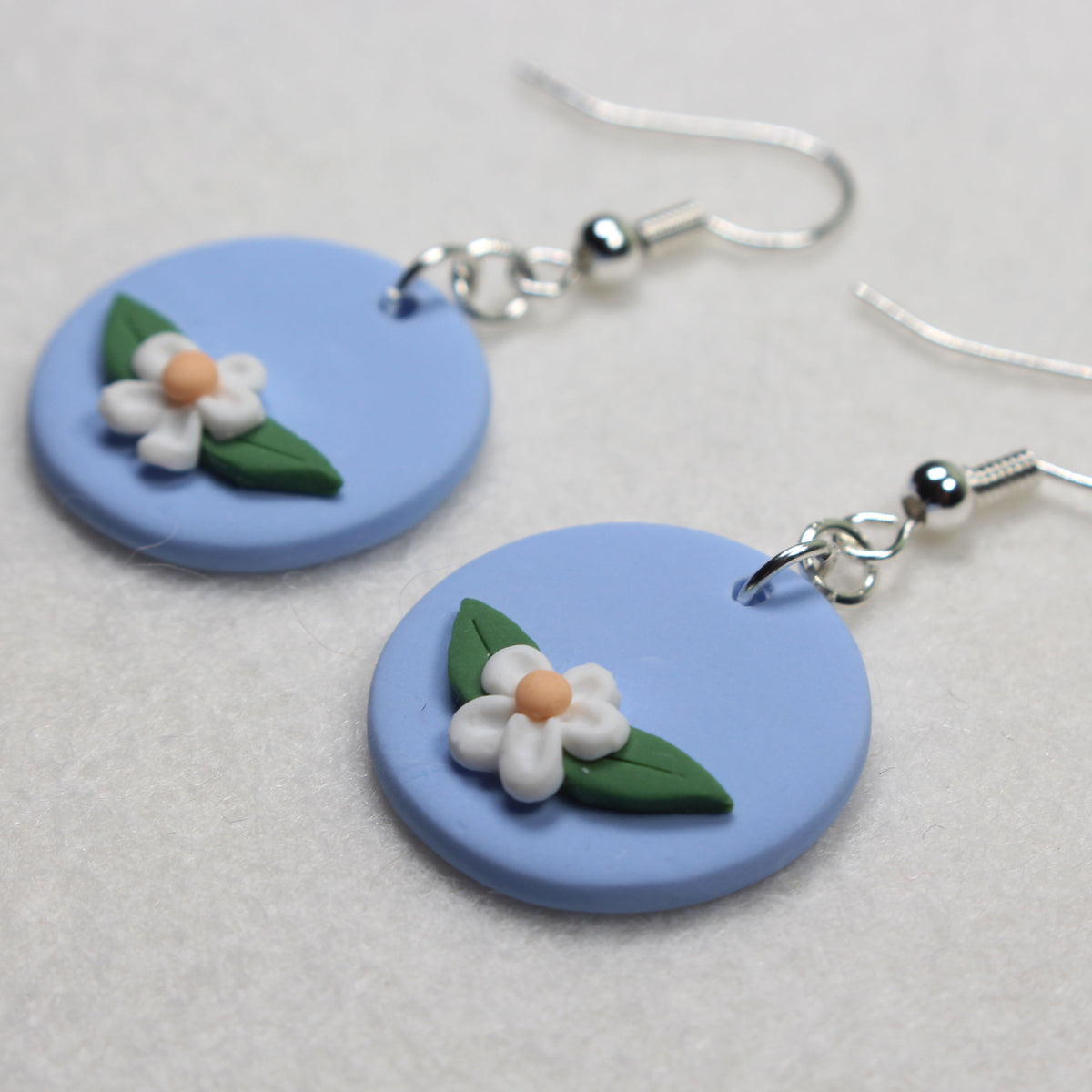 simple nickel free hook earrings. baby blue background with a small white petal daisy in between two leaves