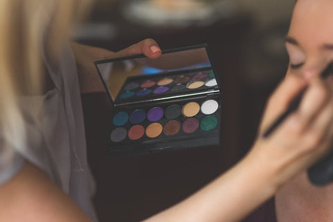 a woman holding a palette of makeup doing another woman's makeup