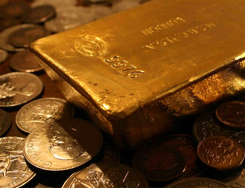 a bar of gold on a pile of gold coins