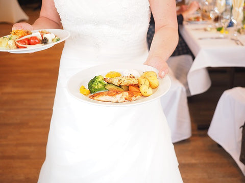 a bride is carrying two plates of food. They are full of various different foods.