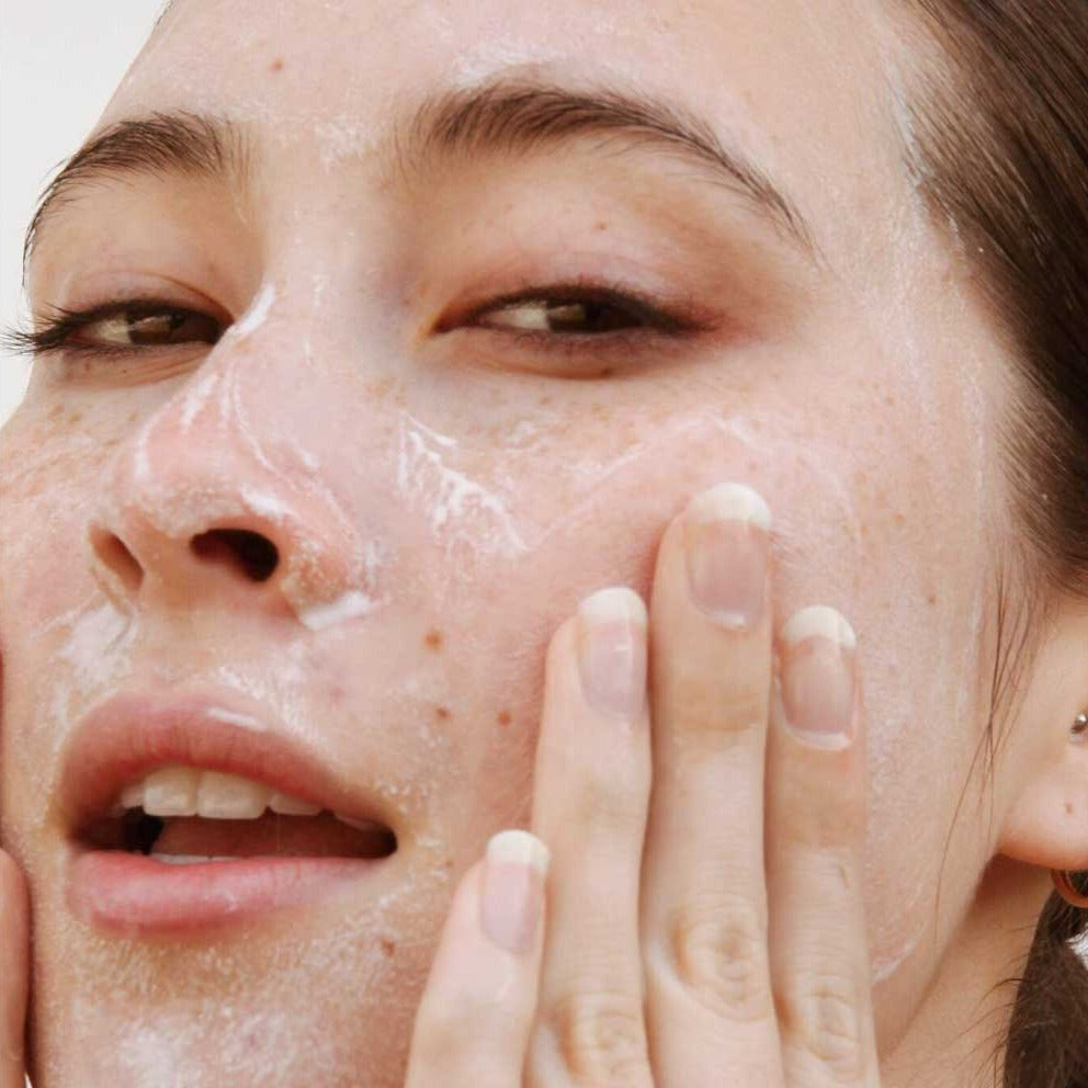 Woman washing face with advanced revitalizing cleanser