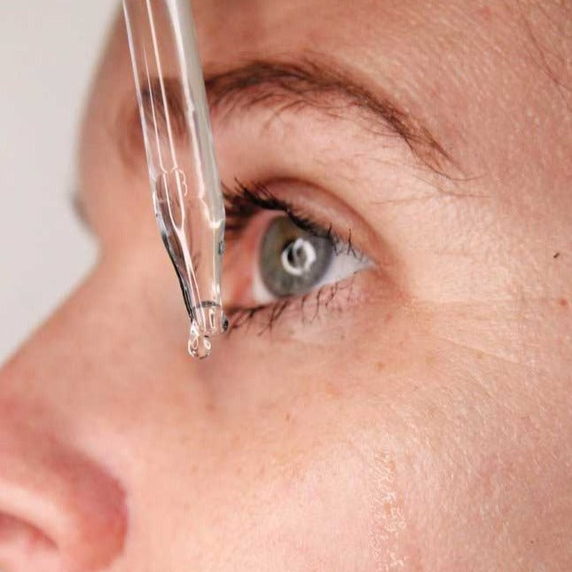 Load image into Gallery viewer, Woman dripping hyaluronic serum onto face