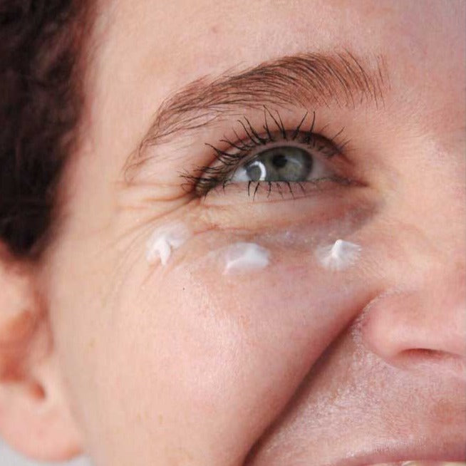 Load image into Gallery viewer, Three dabs of eye cream on smiling womans undereye