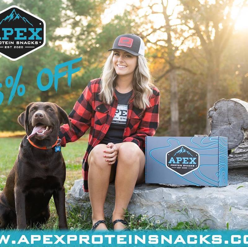 Woman sitting next to a dog and a box of Apex snacks