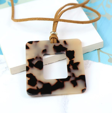 Tortoiseshell resin pendant on long taupe cord