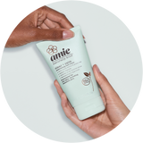 Hands holding Amie clear and calm exfoliating face wash