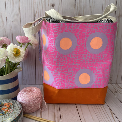 Large drawstring bag featuring a hot pink print on petunia cotton fabric. Dots in the middle makes the design look like eggs