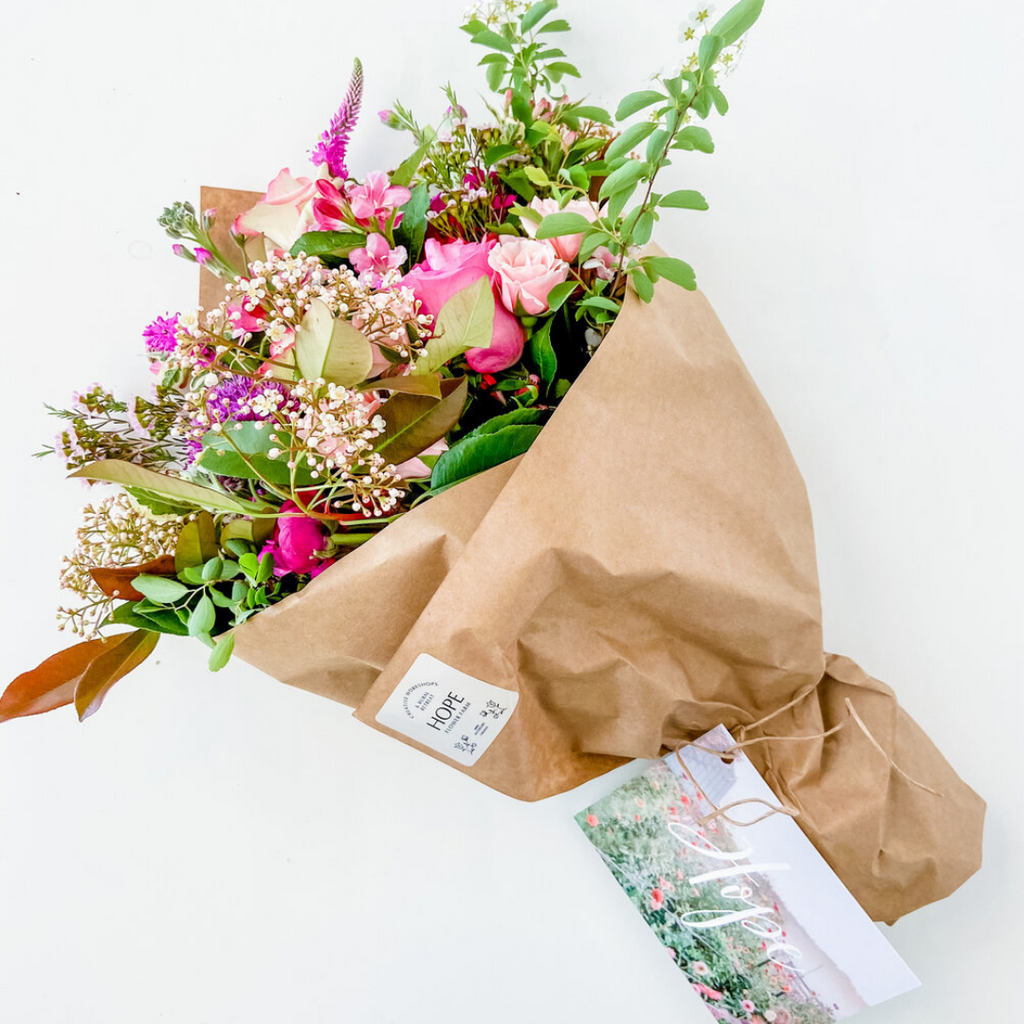lush wrapped bouquet of an assortment of bright stems including babys breath, roses, veronica and greenery wrapped in kraft brown paper Hope Flower Farm Loudoun County local florist near me Waterford Virginia, flower shop