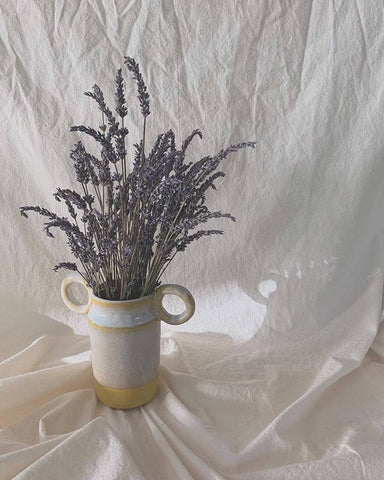 Yellow and white vase with lavender flowers