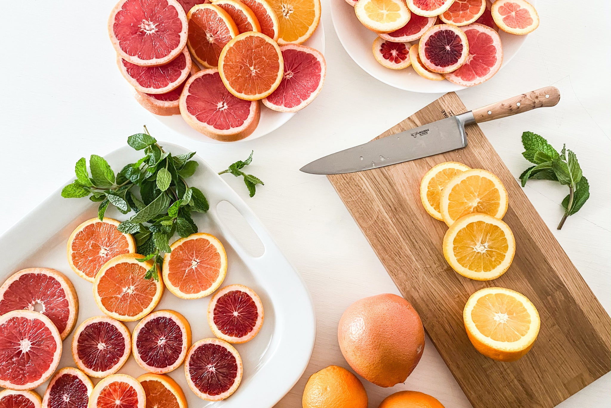 citrus fruits on a cutting board with knife