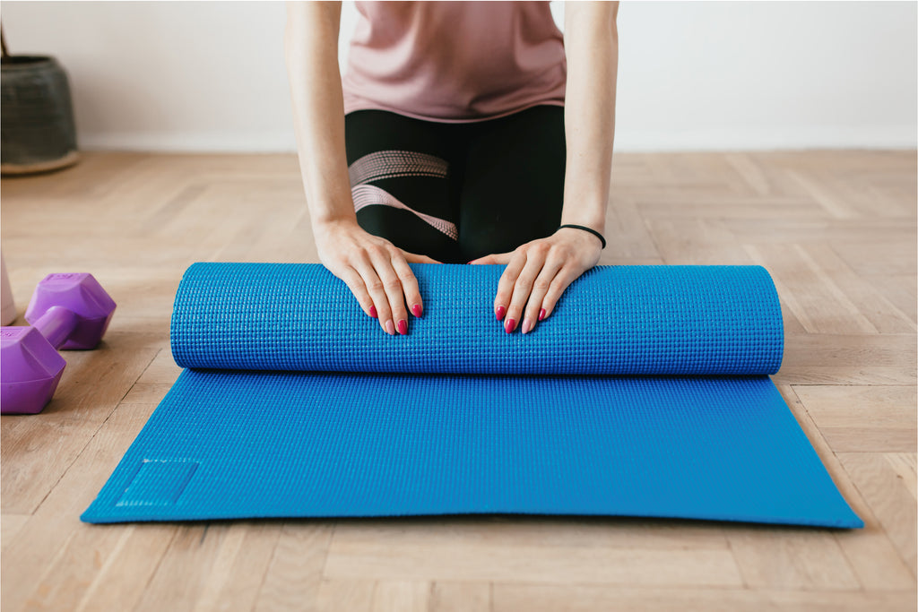 does exercising help sleep? woman rolling yoga mat