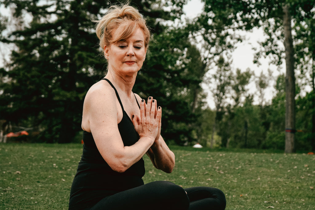 Older woman doing yoga in the park