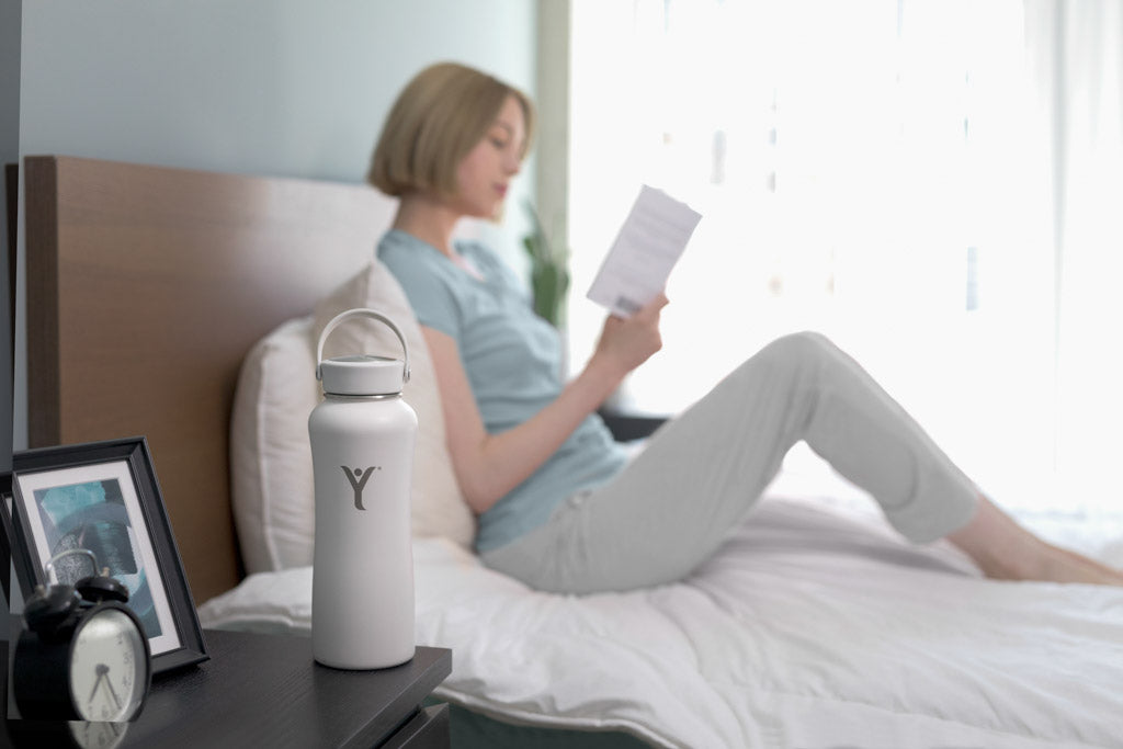 Woman reading in bed by pearl grey insulated bottle