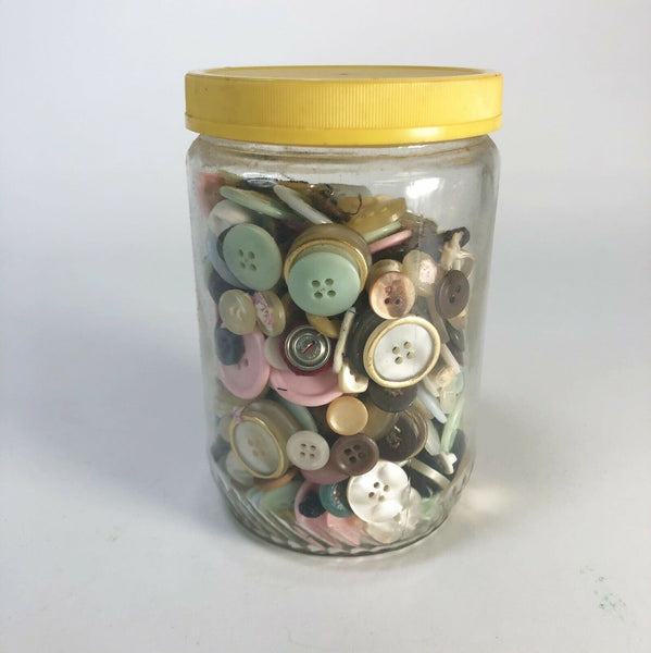 Vintage jar packed full of various vintage buttons