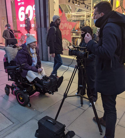 A woman in a purple coat and cream hat sits in her electric wheelchair on a hughstreet outside a shop. A camera man and woman are filming her.