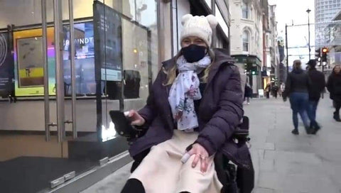 Leanne is in a purple coat and cream hat with a black mask on, on a busy London hughstreet in her electric chair.