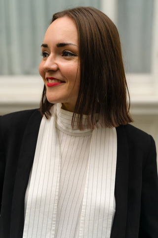 A woman with short brown hair looks to the left of the photo, smiling. She has red lipstick on and winged eyeliner. She is wearing a white pinstripe top with ties that fall either side of her neck under a black blazer.