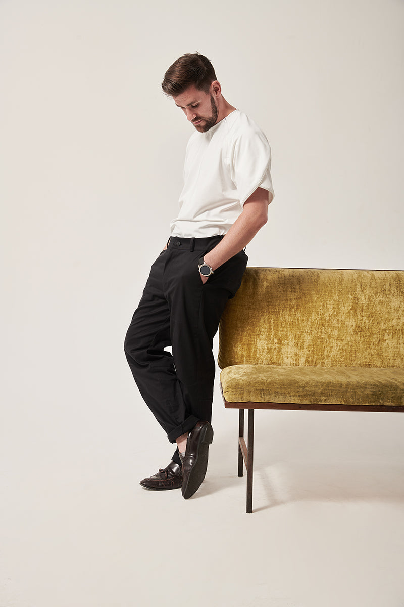 A man with styled dark hair and light facial hair looks at the ground. He leans against a crushed velvet sofa that is moss coloured.  The trousers have invisible zips each side and an elasticated back waistband.