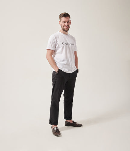 A smiling white man with dark brown hair and dark stubble looks at the camera.  His hands are in his pockets. He is wearing a white t-shirt with Unhidden on it and black trousers. He has brown brogues on.