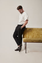Load image into Gallery viewer, A white man stands leaning against a crushed velvet moss coloured sofa, his legs crossed and arms in his pockets. He is wearing a white t-shirt with a wrap sleeve. There are concealed zips to allow chest access at the front.
