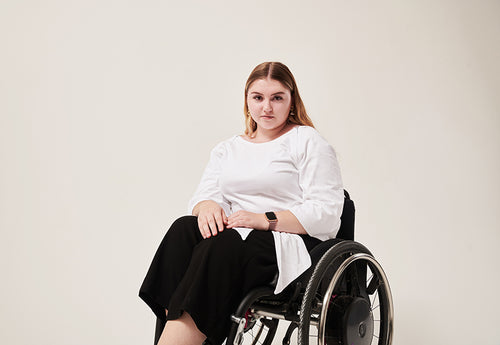 A woman with dark blonde hair in a centre parting looks in to the camera.  She is wearing a white top with concealed zips at the front seams for chest port access, It has wing sleeves and the back wraps over and ties back to the front.  She is sat in a manual wheelchair.
